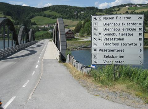 veiskilt som viser hvilke steder man finner på den andre siden av broen i bildet