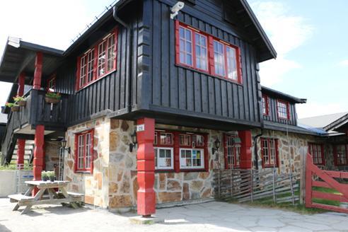 en brunbeiset bygning med røde kanter og vinduskarmer som står på en stor steinmur