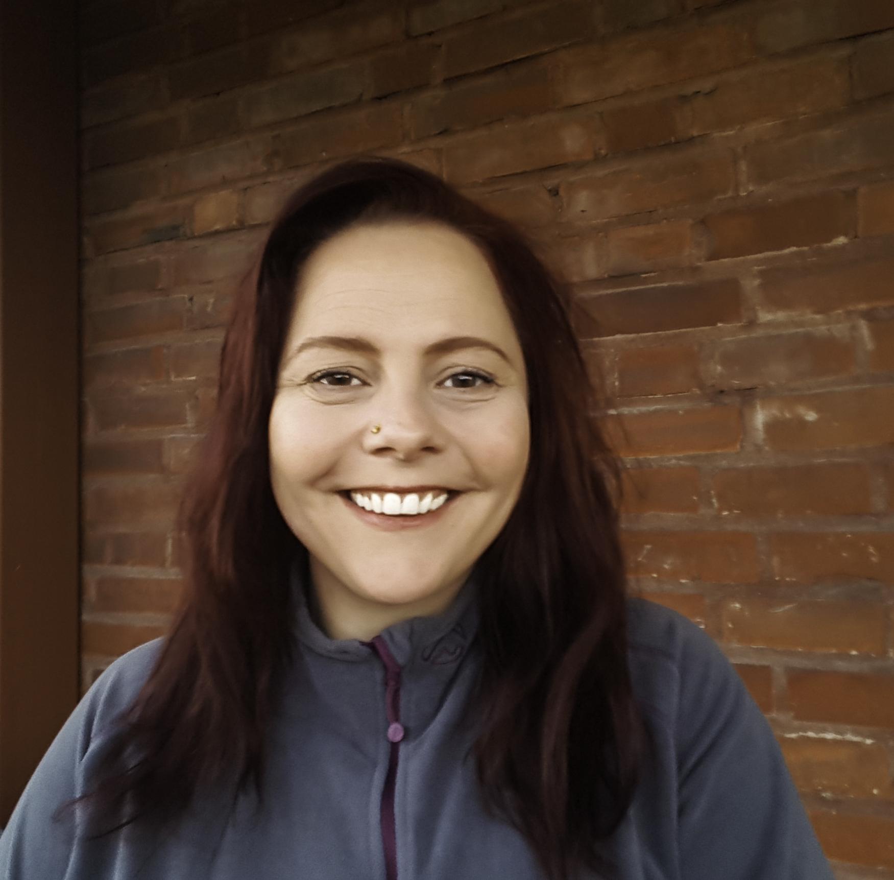 Et portrett av en smilende kvinne med langt mørkt hår mot en teglsteinsbakgrunn.
