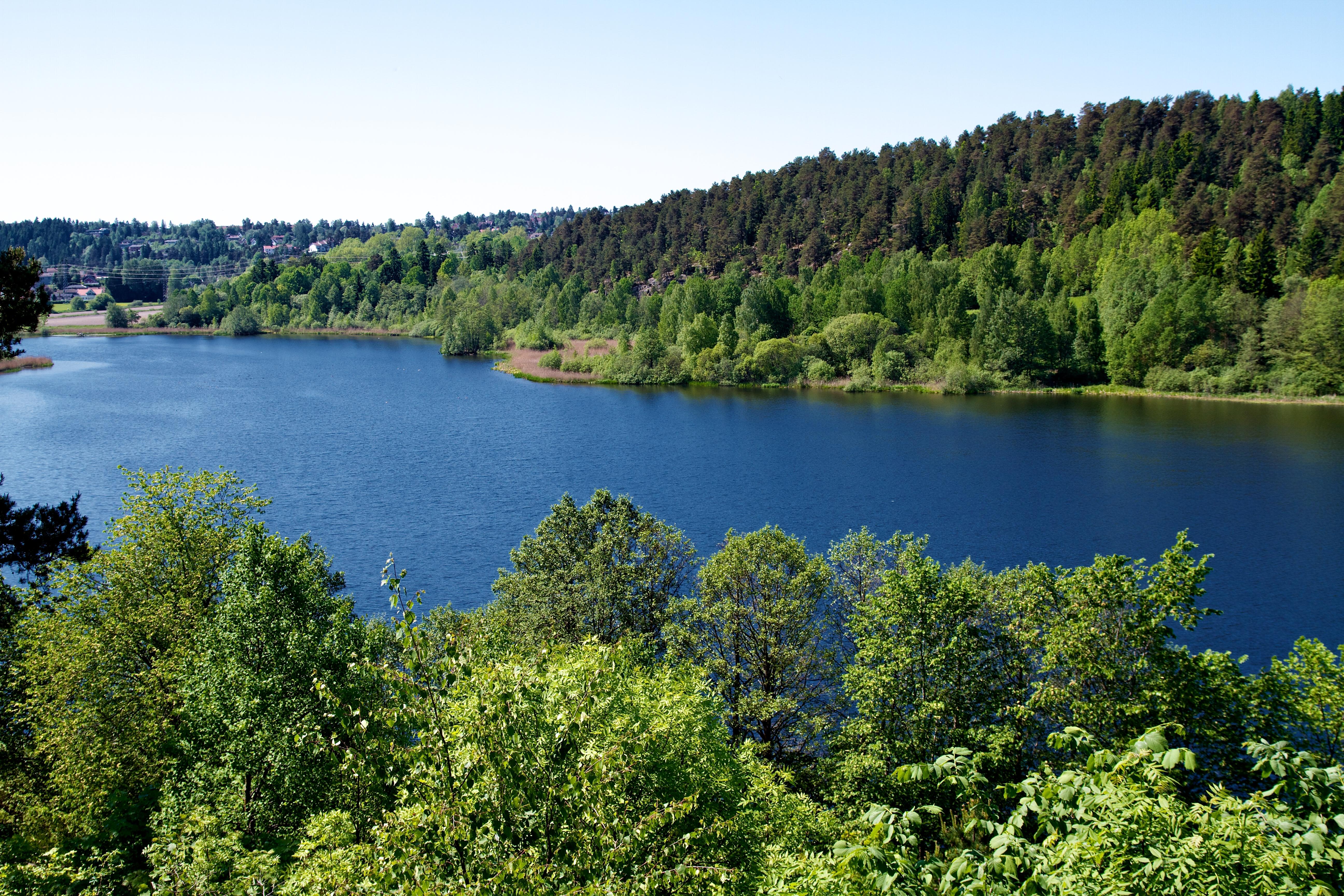En innsjø som ligger mellom grønne høyder.