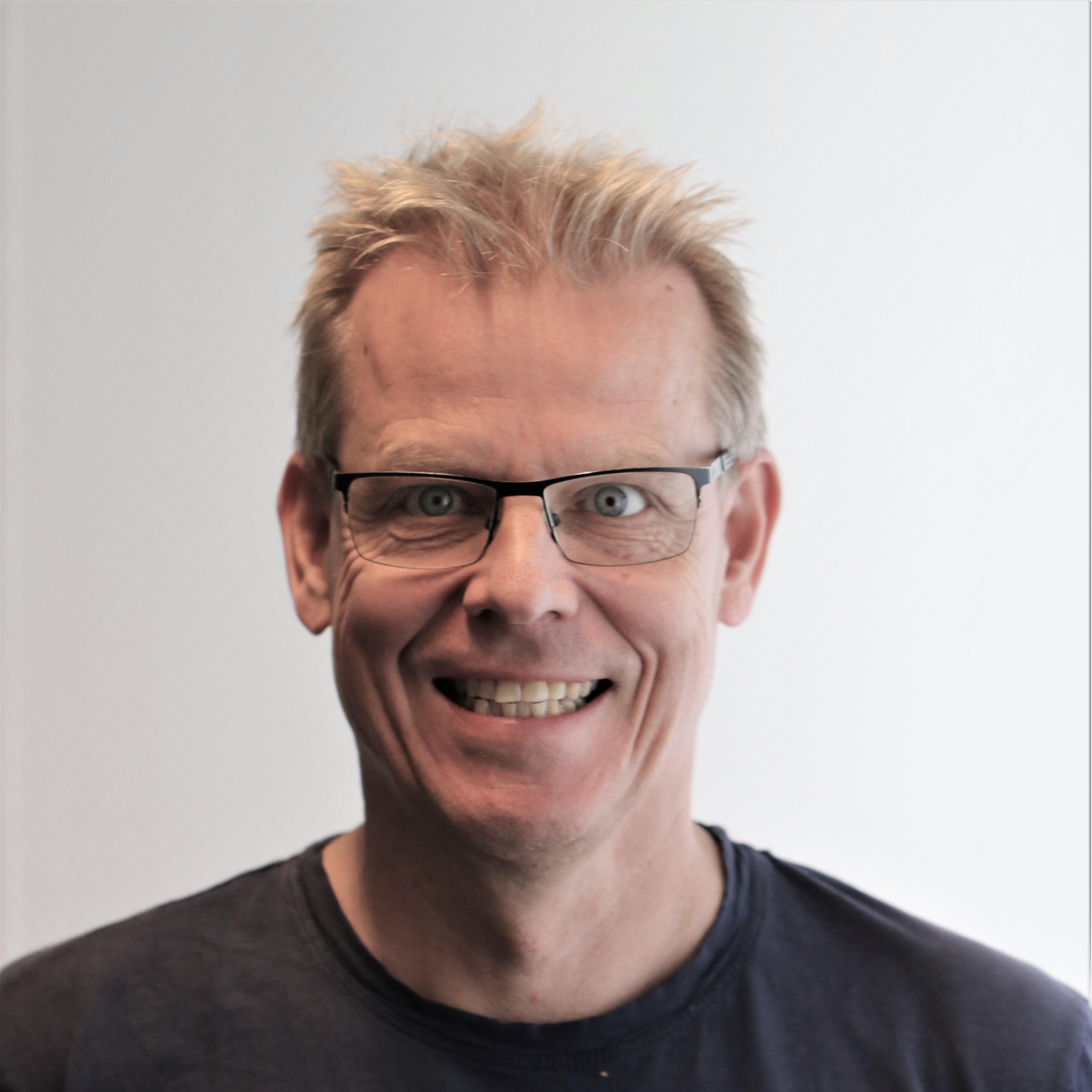 Et portrett av en smilende mann med briller og lyst hår.