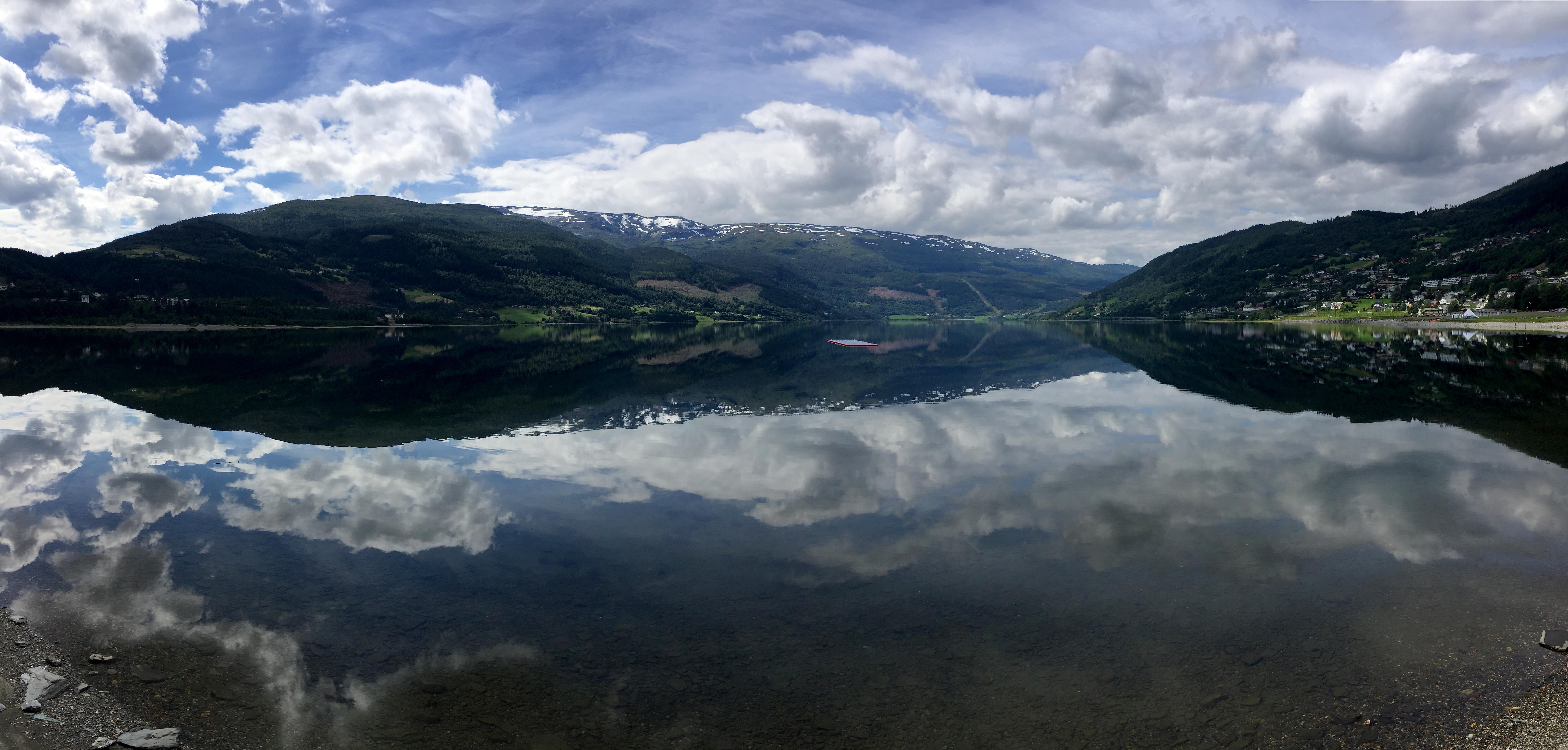 Utsikt over en innsjø med fjell i bakgrunnen.